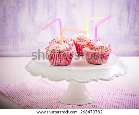 Lemonade cupcakes: cakes with frosting decorated with sprinkles and cocktail straws - stock photo