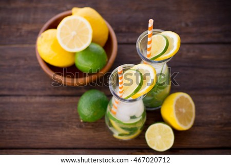 Lemonade drink. Lemonade in the jug and lemons with mint on the table outdoor