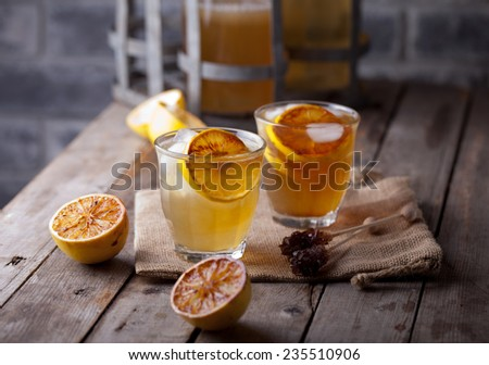 Lemonade in glasses and bottles made of grilled lemons on a wooden background.  - stock photo