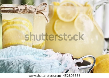Lemonade in mason jars with extreme shallow depth of field. Fresh lemons and pitcher of fresh juice in background. - stock photo