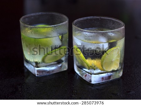 Lemonade served on a dark marble bar top garnished with a lime view 1 - stock photo