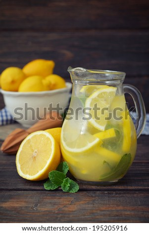 Lemonade with fresh lemon and mint in glass jug on wooden background - stock photo