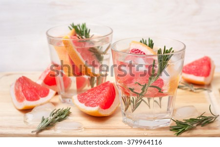 lemonade with grapefruit and rosemary, ice in glasses on a wooden background - stock photo