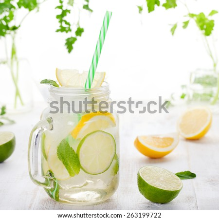 Lemonade with ice, lemon and lime slices in a jar with straw in a white summer wooden background - stock photo