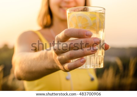 lemonade yellow vitamin energy and useful nutritional of lemon slices with lemon, lime, orange in the hand of a young girl in a yellow sports shirt on blurred background nature