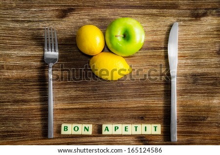Lemons and apple on wooden vintage table with silverware and Bon apetit sign - stock photo