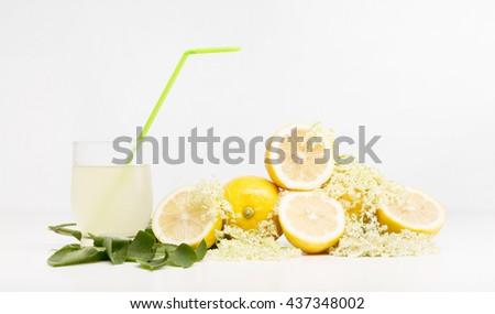 Lemons and elder flower arrangement on a white table with lemonade    - stock photo