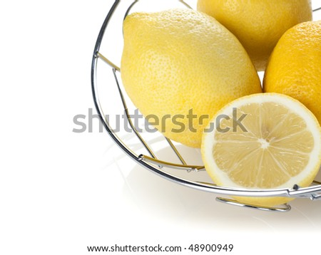 lemons and piece in chrome basket on white surface, horizontal