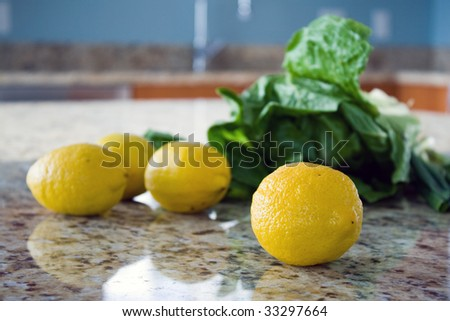 Lemons and salad leaves on a kitchen countertop.
