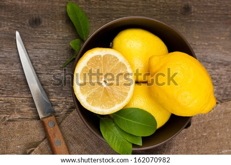 lemons in a bowl on wooden background - stock photo