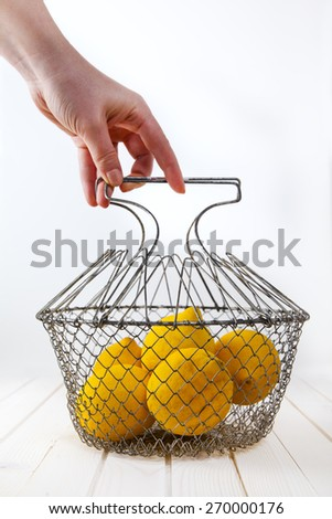 lemons in basket in hand - stock photo