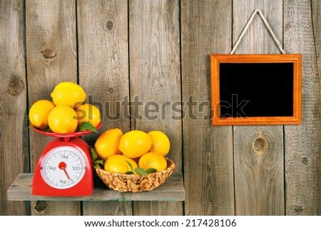 Lemons on scales and in a basket on a wooden shelf. A framework on a wooden background. - stock photo