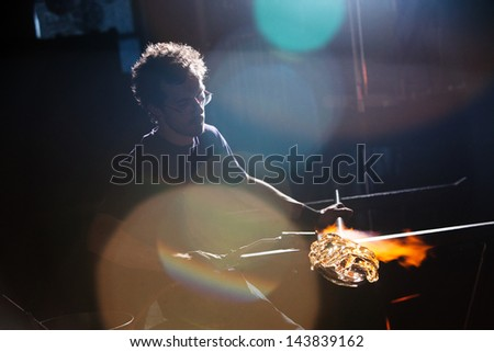 Lens flares surround glass worker creating vase - stock photo
