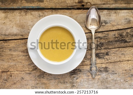 Lentil cream soup with silver spoon on wooden background. Top view image - stock photo