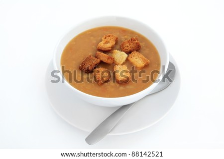 Lentil soup with croutons in a white porcelain bowl with plate and ...