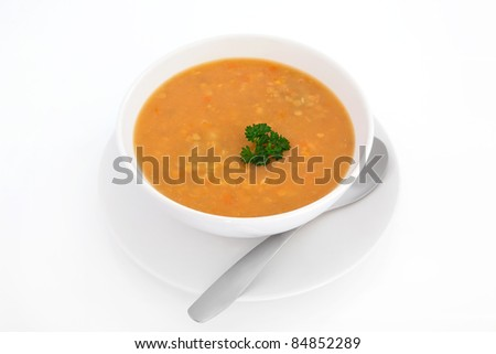 Lentil soup with parsley leaf sprig in a white porcelain bowl with plate and spoon isolated over white background. - stock photo