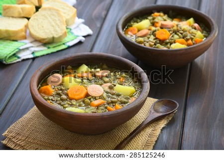 Lentil soup with potato, carrot, onion, sausage slices, with slices of baguette bread in the back, photographed on dark wood with natural light (Selective Focus, Focus on the middle of the first soup)
