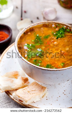 Lentil soup with smoked paprika and bread in a ceramic bowl on a wooden background - stock photo