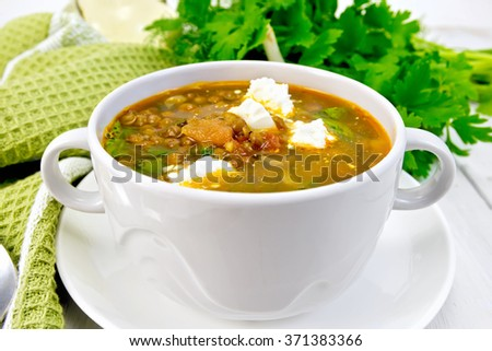 Lentil soup with spinach, tomatoes and feta cheese in a white bowl, spoon on a napkin, parsley on the background light wooden boards