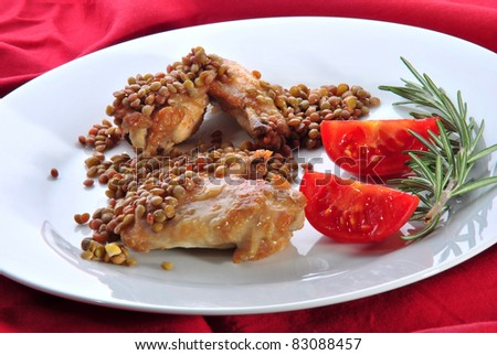 Lentils and grilled chicken wings with tomatoes and rosemary