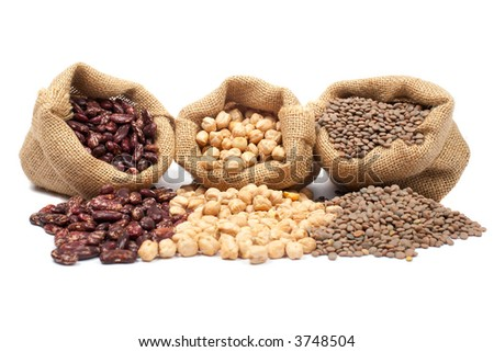 Lentils, chickpeas and red beans spilling out over a white background. - stock photo