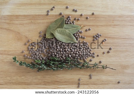 Lentils, thyme and bay leaves on wooden board from directly above. - stock photo