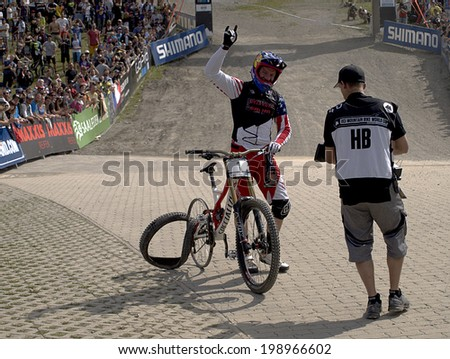 LEOGANG, AUSTRIA - JUNE 15, 2014: Aaron Gwin of Specialized Racing DH is cheered by the spectators after finishing his run on a rim at the UCI Mountain Bike Downhill World Cup in Leogang.