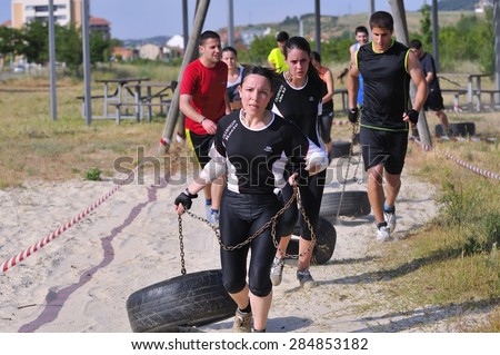 LEON, SPAIN - JUNE 6: Farinato Race, extreme obstacle race in June 6, 2015 in Leon, Spain. People jumping, crawling,passing under a barbed wires or climbing obstacles during extreme obstacle race. - stock photo