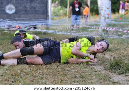 LEON, SPAIN - JUNE 6: Farinato Race, extreme obstacle race in June 6, 2015 in Leon, Spain. People jumping, crawling,passing under a barbed wires or climbing obstacles during extreme obstacle race.