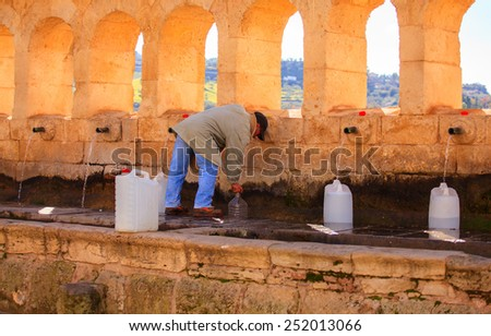 LEONFORTE, ITALY - JANUARY, 08: Man filling cans with fountain water on January 08, 2015 - stock photo