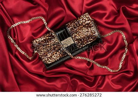 Leopard lacquer bag lying on a red silk, as background - stock photo