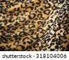 Leopard skin background - brown and black fabric with drapery - stock photo