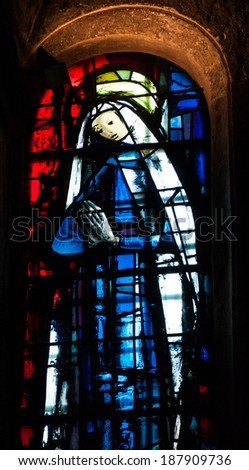 "LES BAUX-DE-PROVENCE, FRANCE - MAY 16, 2013:  Stained glass window with praying Madonna in Saint Vincent's Church in Les Baux-de-Provence, one of ""The Most Beautiful Villages of France"". - stock photo"