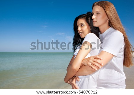 Lesbian couple at the beach, holding each other - stock photo