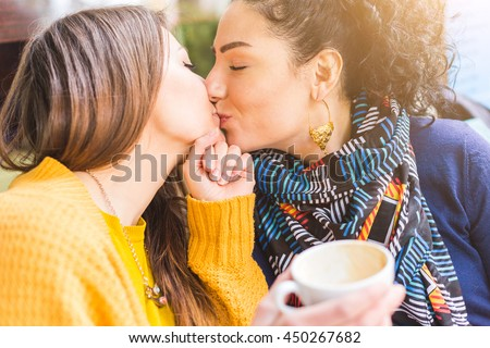 Lesbian couple kissing at a cafe. The young women are having a coffee together and give each other a passionate kiss. Candid situation with real people. Homosexuality and lifestyle concepts. - stock photo