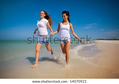 Lesbian couple running on a beach - stock photo