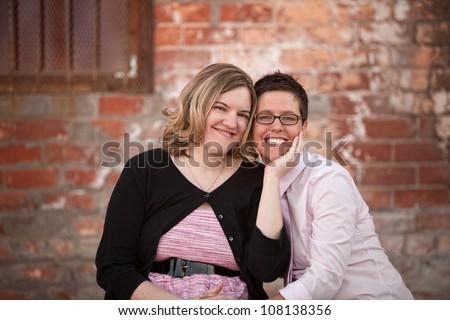 Lesbian couple sitting next to each other outdoors - stock photo