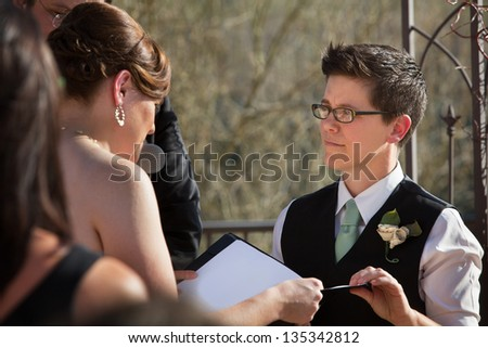 Lesbian partners reading marriage vows in ceremony