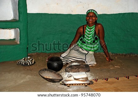 LESEDI CULTURAL VILLAGE,SOUTH AFRICA - JAN 1:Zulu woman in handmade dress cooking maize meal at tribal house on January 1,2008 at Lesedi Village, South Africa.Maize meal is basic Zulu ingredient. - stock photo