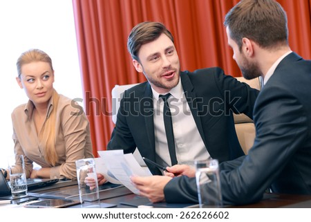 Let me explain. Young attractive business partners in formalwear discuss data sitting by the table at the meeting  - stock photo