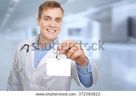 Let me introduce myself. Attractive young doctor showing his name tag. Copy space on the name tag can be used for your text. - stock photo
