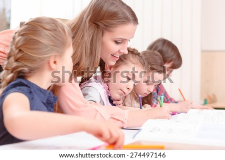 Let me see. Young attractive female teacher leaning to pupils and checking their work - stock photo
