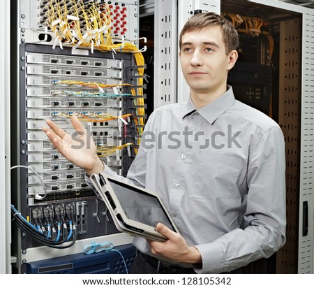 Let me show. The telecom engineer stand in data center and show telecommunication equipment - stock photo