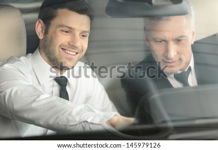 Let me show you all the features. Handsome young classic car salesman sitting at the front seat of the car showing the features to a client - stock photo
