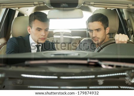 Let me show you the advantages of this model. Confident young salesman showing all the car features to the customer - stock photo