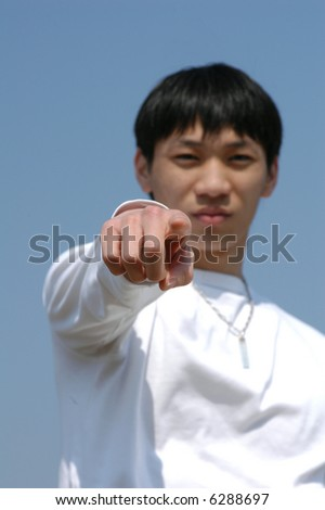 Let's Do It! Young Asian man pointing forward - hand in focus - stock photo