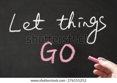 Let things go words written on blackboard using chalk - stock photo