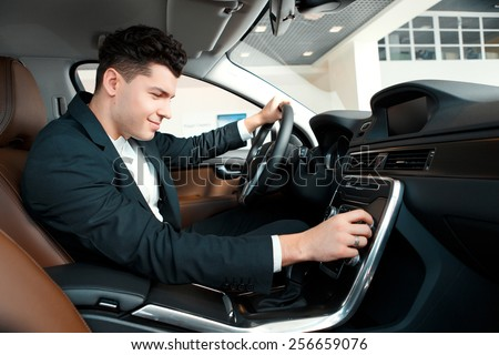 Let us go for a ride. Handsome young businessman examining the car at the dealership while sitting inside the new car and touching the gear box