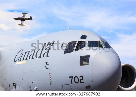 LETHBRIDGE CANADA 25 JUN 2015: International Air Show. A  Canadair T-33 Shooting Star flying  at the Canadian Wings Over North Lethbridge event.   Canadian Air force troop carrier in foreground.  - stock photo