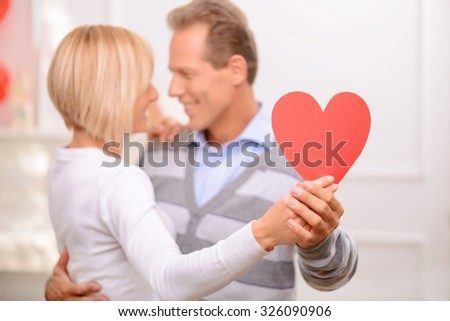 Lets dance. Close up of heart in hands of happy adult couple holding it and dancing on the background  - stock photo